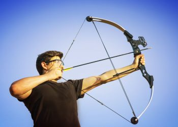 Adult man in black shirt aiming his bow