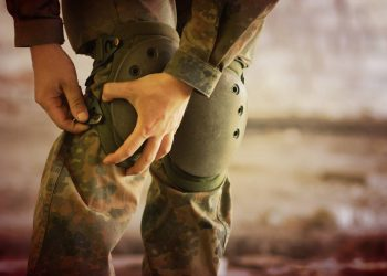 military man fixing his military knee pads