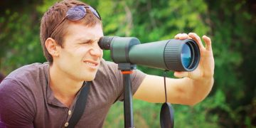 man peeping in a moss-green colored spotting scope