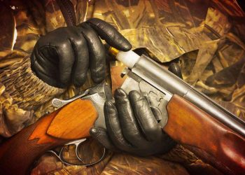 the shooter inserts the cartridge into the double-barrel shotgun wearing a black shooting gloves