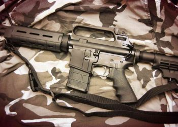 rifle with black sling on a camouflage cloth