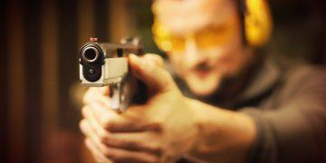 a man wearing an ear gear pointing his gun