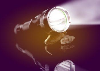 Black flashlight with lights open on stones mirroring on black background