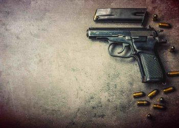 pistol gun and bullets strewn on the table