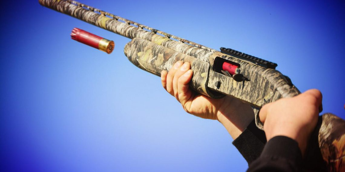 Camouflage shotgun with casing flies out of a shotgun