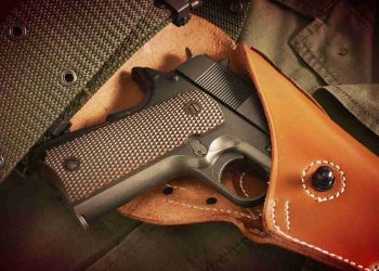 pistol in a holster and belt lie on military jacket closeup