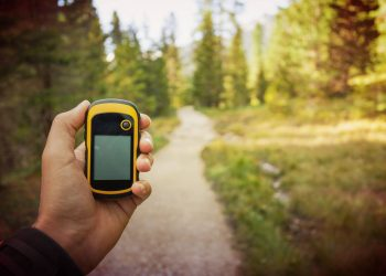a hiker's hand holding a gps in finding the right direction