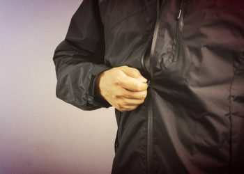 cropped man wearing a black jacket holding the zipper