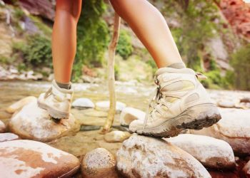 woman hiker crossing on a river creek wearing her hiking shoes