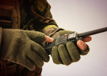 soldier's hand holding a digital device transmitter device