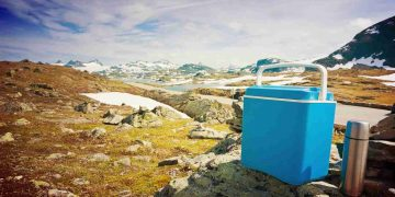 blue cooler for camping on a rocky area
