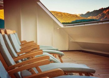open cushioned wooded deck lounge chairs at sunrise
