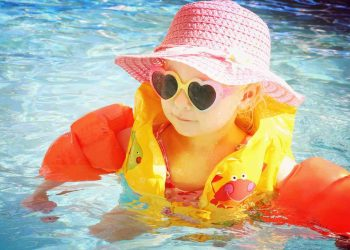 toddler girl is swimming the pool with arm floaties and a safety life vest