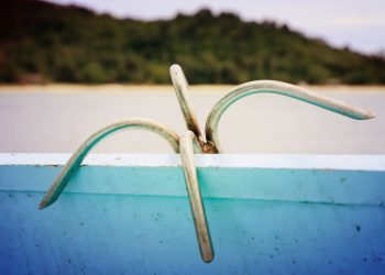 anchor in a traditional wooden boat on the sea with island background