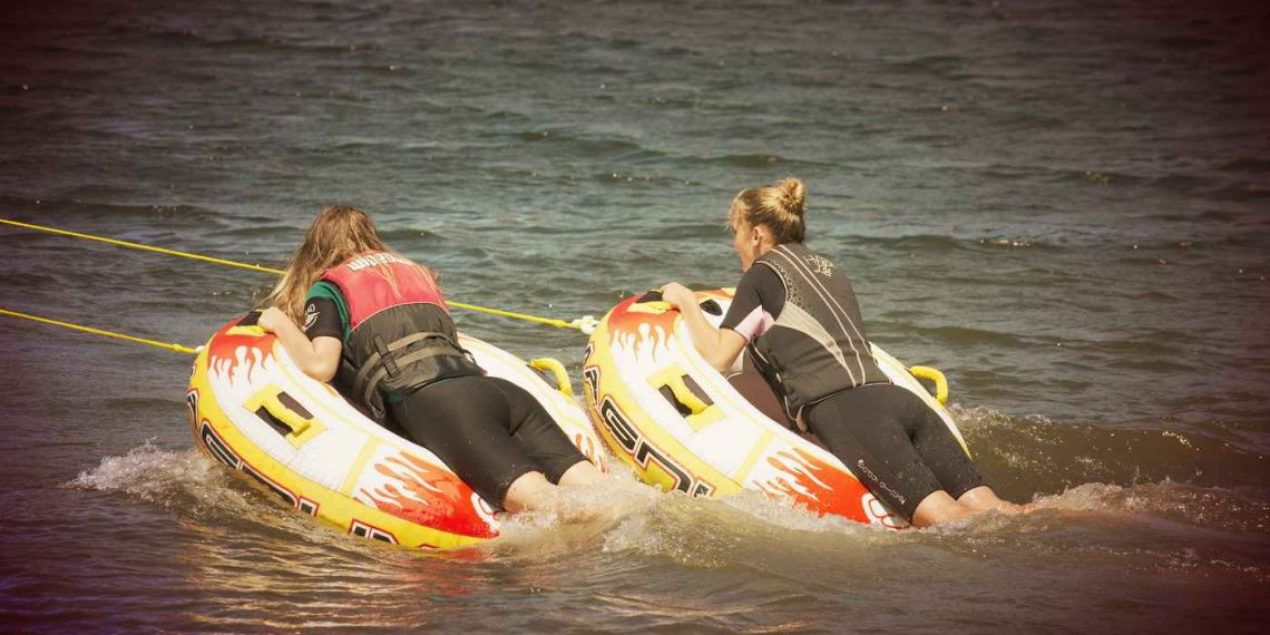 inflatable towable tubes with two girls riding on it in the water