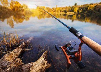 Fishing rod near beautiful pond