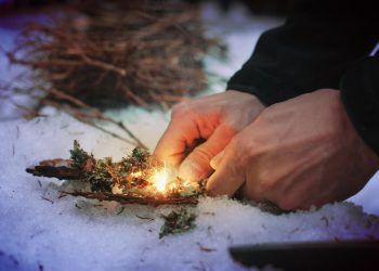 man outdoors in the snow lighting a fire