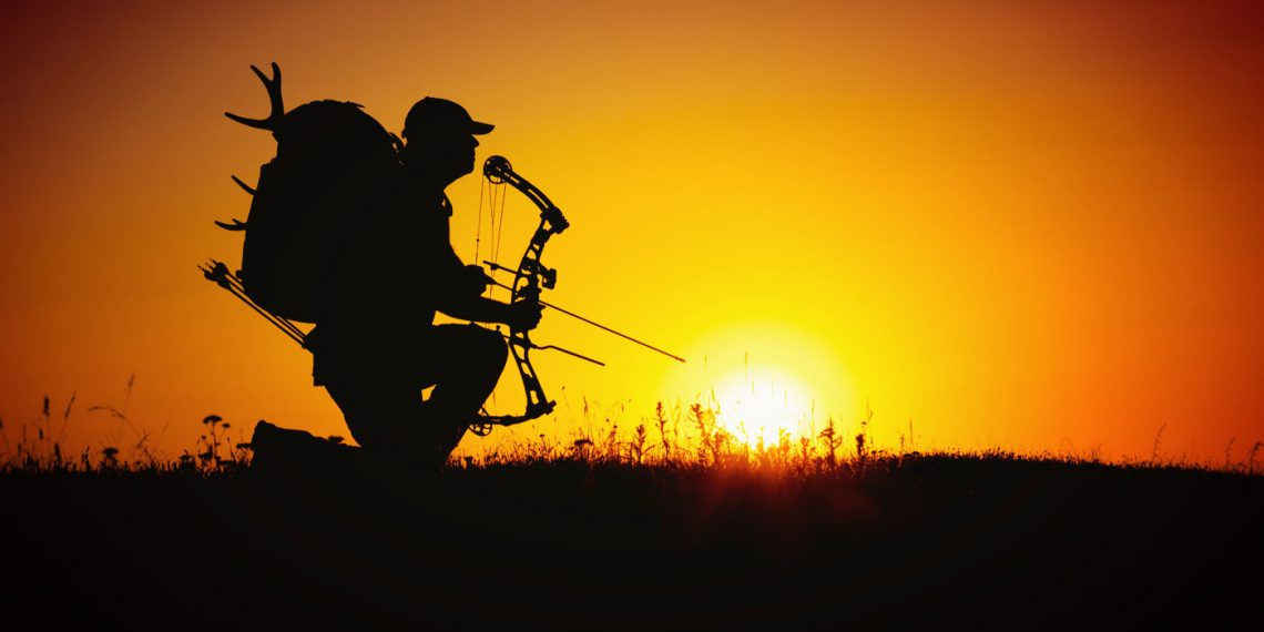 hunter holding his bow with the sunset behind him