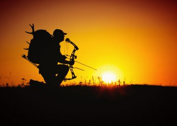 hunter holding his bow with the sunsetbehind him