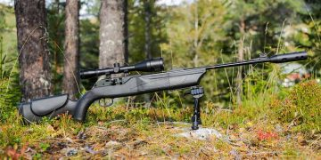 rifle on a bipod outside in the forest