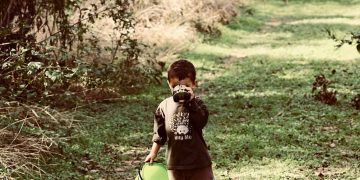 kid outside with binoculars and a bucket