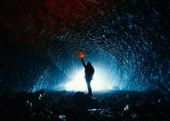 person in a cave with a torch