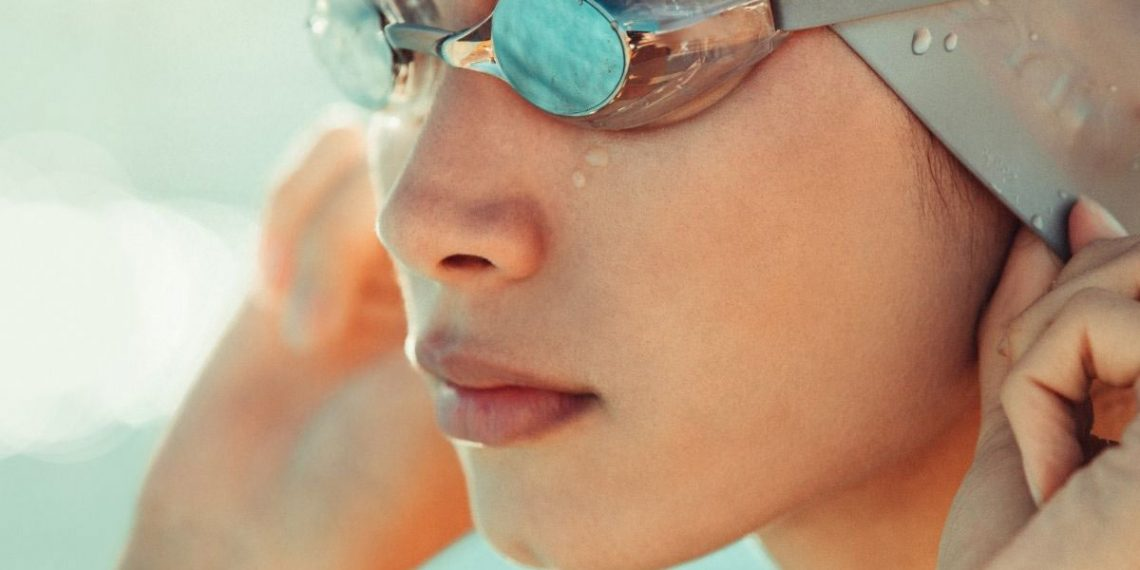 woman putting on her swim cap and goggles